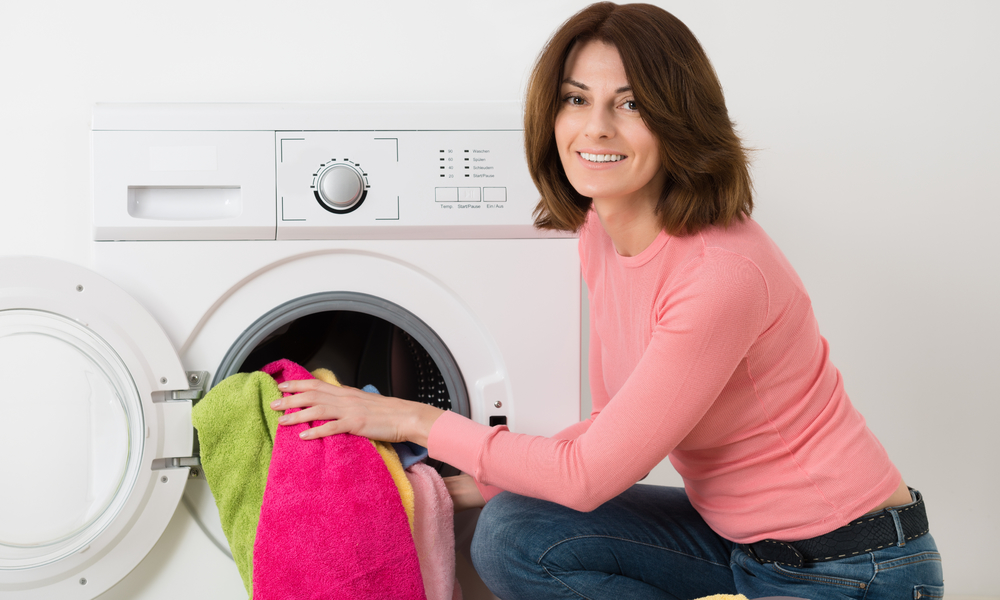 woman in pink shirt removing colorful towels from dryer