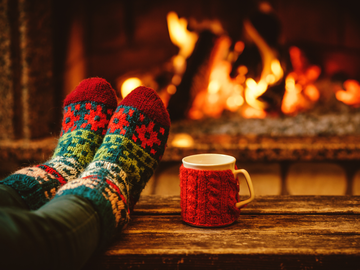 Feet up, resting in front of fire with cozy socks and a hot drink