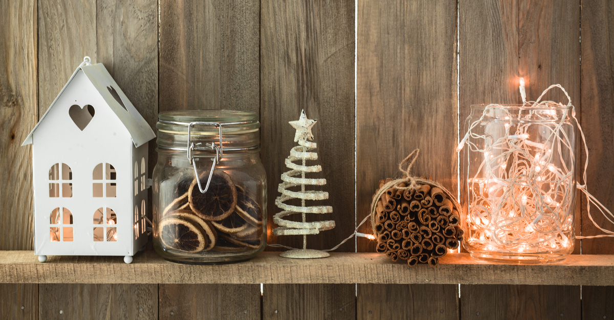 holiday decorations with tree, cookies, bundle of cinnamon sticks, lights, and a hose with a candle inside